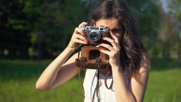 Fiatal felnőtt nő fotós bevétel mozi és fénykép-val fényképezőgép a szabadban.