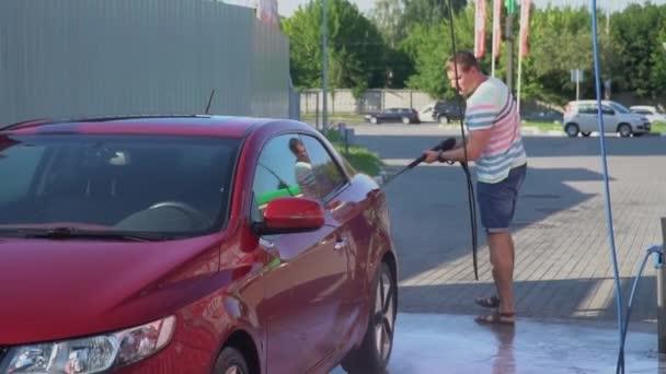 Kavkazské mladík mytí jeho auto na mytí aut, samoobslužné služby. Mytí aut.
