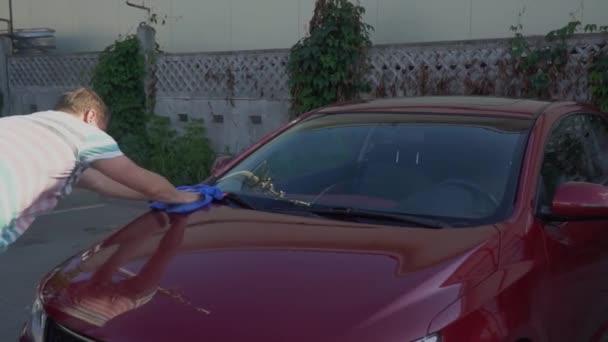 Kavkazské mladík mytí jeho auto na mytí aut, samoobslužné služby. Mytí aut