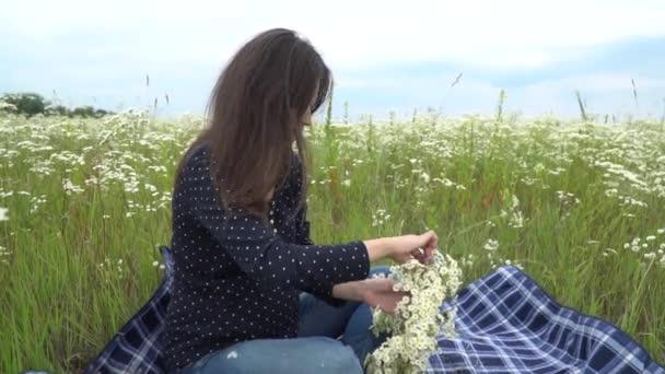 Happy pregnant woman making camomile wreath.