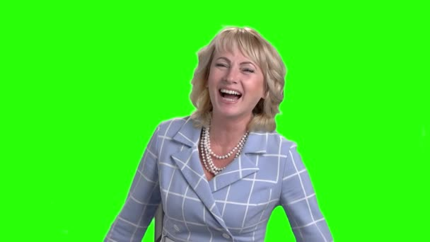 Mature woman is laughing on green screen.