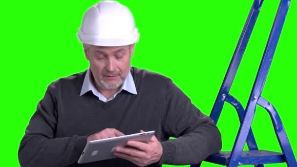 schöner reifer Vorarbeiter mit digitalem Tablet.