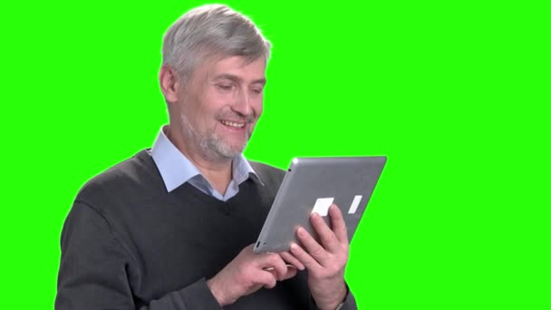 Smiling mature man talking via internet.