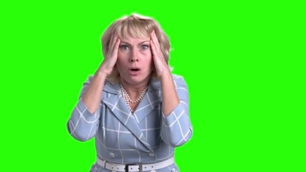 Horrified mature woman on green screen.