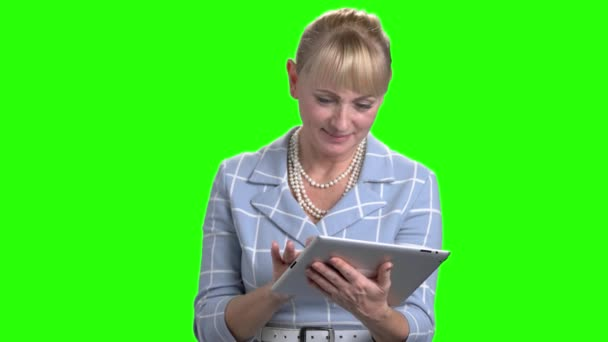 Caucasian mature woman using digital tablet.