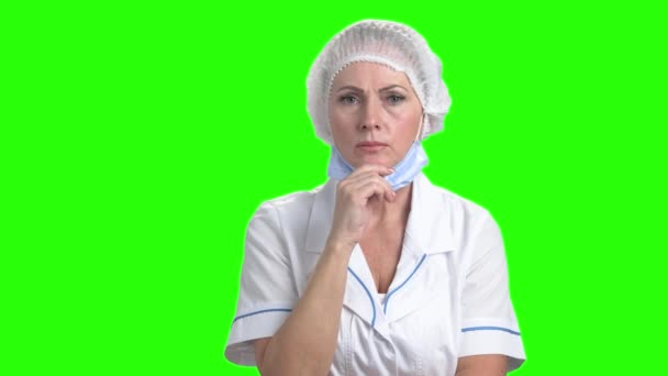 Shocked female doctor on green screen.