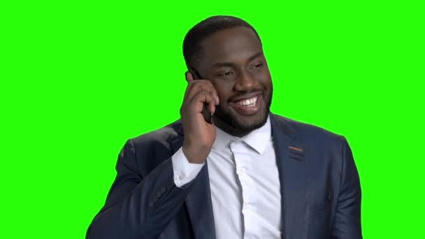 Cheerful afro american businessman talking on phone.