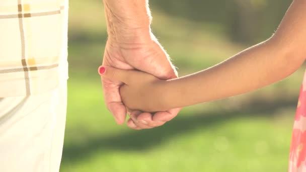 idős férfi és gyerek kéz a kézben.