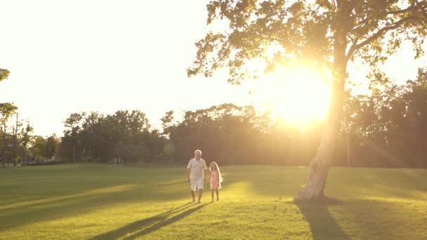 Elderly man and little girl outdoors.