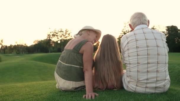 Senioři a vnuka na pozadí přírody