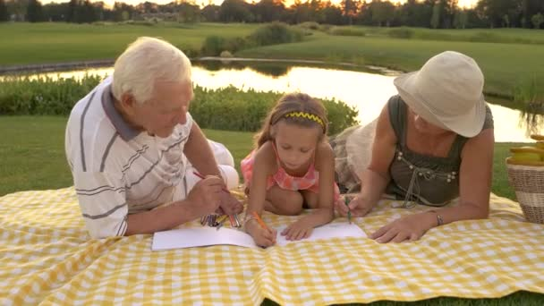 Grandparents and granddaughter drawing together.