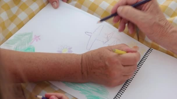 Hands of girl and grandparents drawing together.