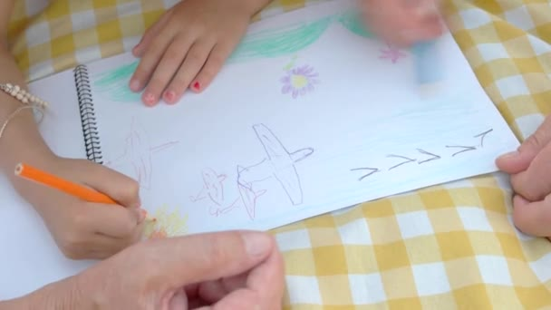 Hands of child and elderly man drawing.