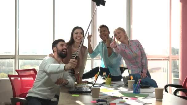 Spolupracovníků s foto usind selfie stick a hrát opice.