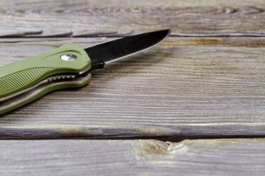 Clasp-knife on wood, close up.