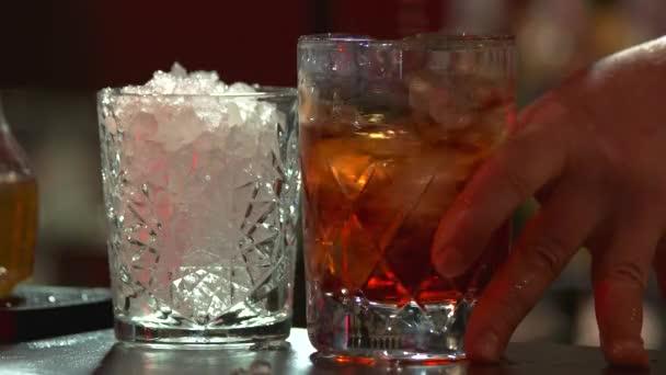Za stálého míchání whisky s ledem, zblízka.