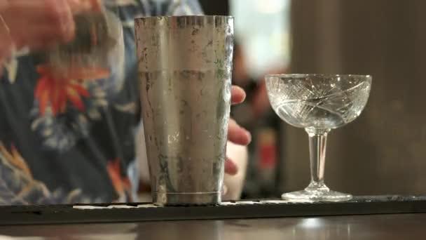 Barman stékal šejkr na koktejl. Náplň champagne talířek, zblízka.