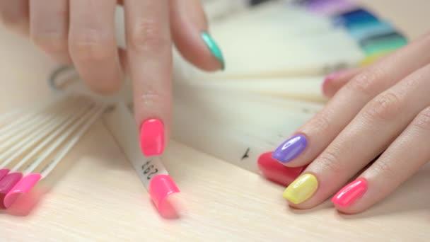 Manicured hand choosing nail polish.