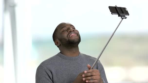 Funny dark-skinnesd guy using monopod.