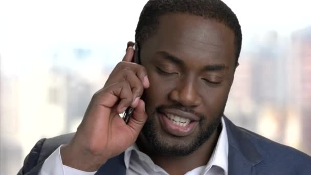 Cheerful afro-american entrepreneur talking on phone.