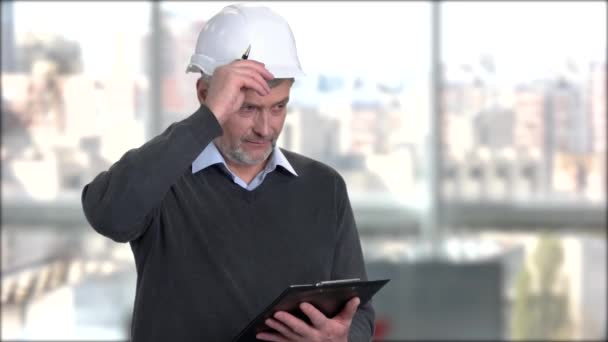 Mature engineer in hard hat writing on clipboard.