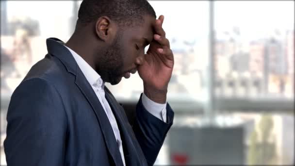 Tired dark-skinned businessman having migraine.