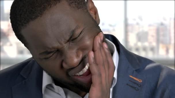 Gestresster Mann leidet unter Zahnschmerzen.