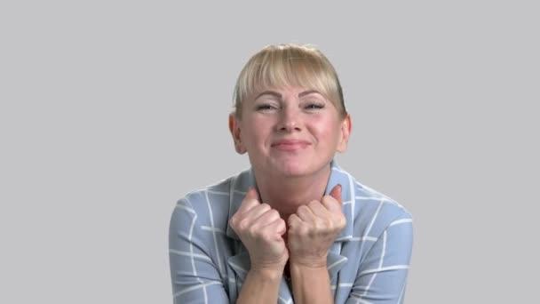 Face of joyful woman on gray background.