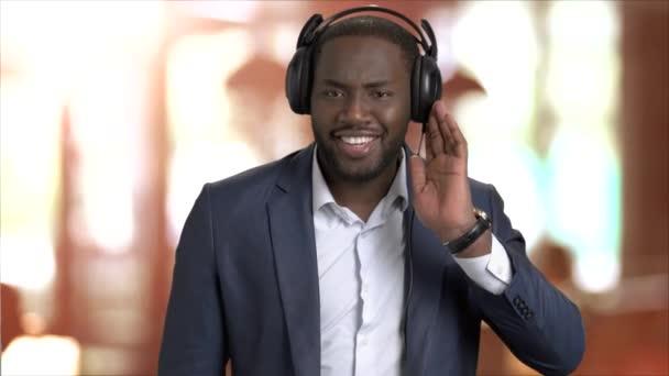 Joyful businessman listening to music in headphones.