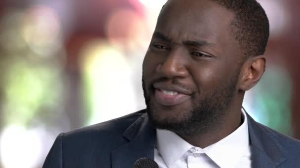 Fekete férfi mikrofonba beszél közelről
