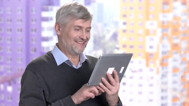Mature man using computer tablet.