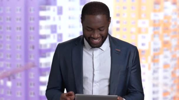 Smiling black businessman using computer tablet.