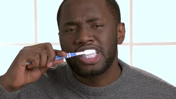 Afričan-americká chlap je čištění zubů.