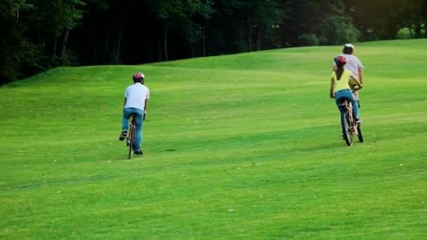 Tři mladí přátelé na kole v parku