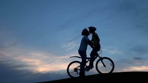 Mladý pár líbání na kole při západu slunce
