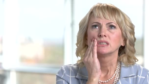 Mature businesswoman suffering from toothache.