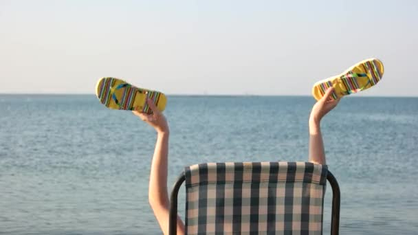 Woman sitting in chaise lounge and waving her flip flops.