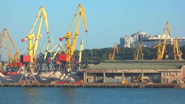 průmyslový přístav s jeřáby a loděmi.