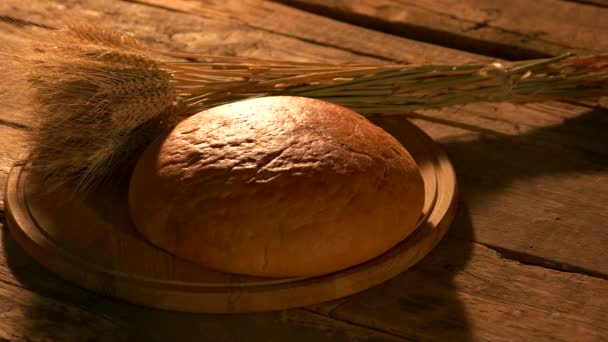Loaf of round yellow bread and wheat ears.