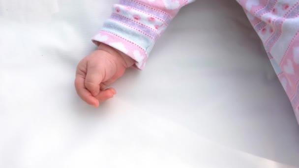 Ruka novorozené holčičky na bílý koberec