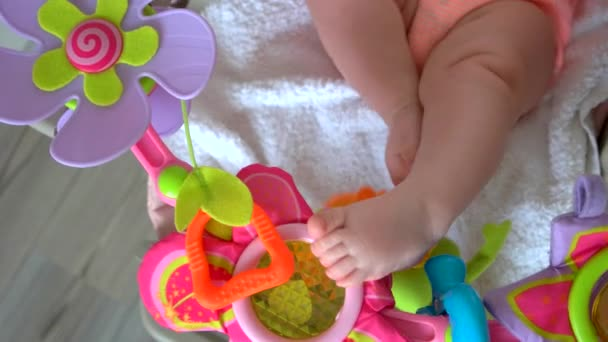 Newborn baby legs and toys.