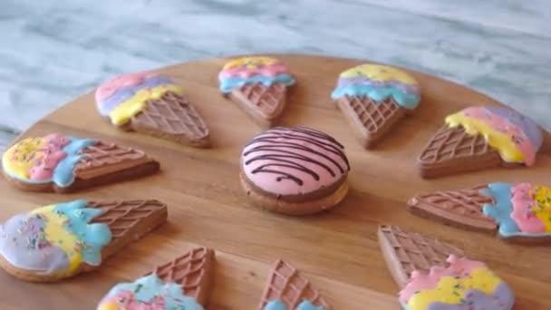 Barevné zasklené sušenky na dřevěné desce.