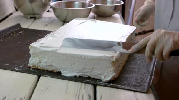Baker, pokrývající dort se šlehačkou.