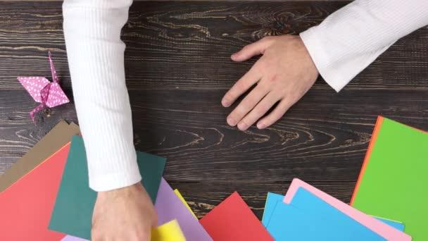 Mužské ruce, přičemž zažloutlý papír
