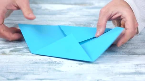 Tvorbě figurky origami s modrým papírem.