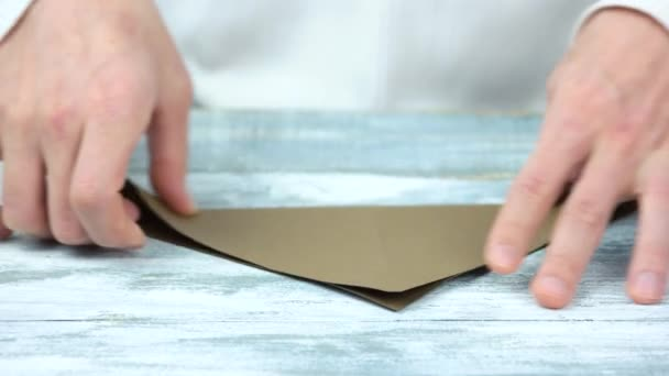 Male hands creating origami with brown paper.