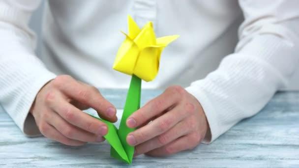 Muž dělat žluté origami květina.