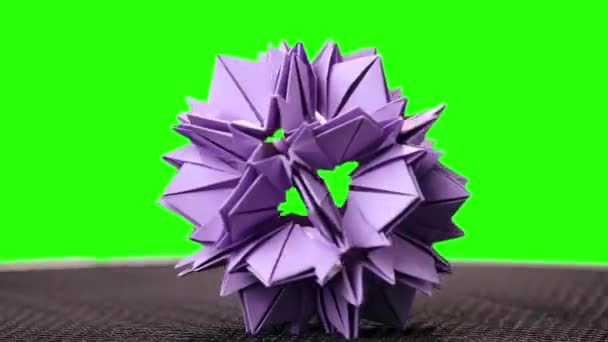 3d purple origami spiky ball exposition. Green hromakey background for keying.