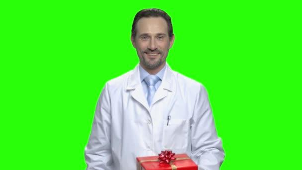 Pohledný doktor prezentovat darem pro vás. Červené pole s stuhou luk. Hromakey pozadí pro Klíčování zelené obrazovky.