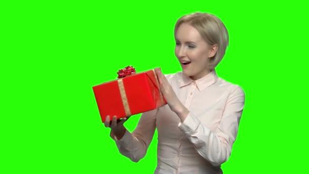 Frau schüttelt Geschenkbox vor Aufregung.